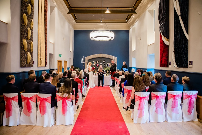 Guests awaiting the arrival of the bride in a room lavishly decorated for a wedding at Edinburgh Castle