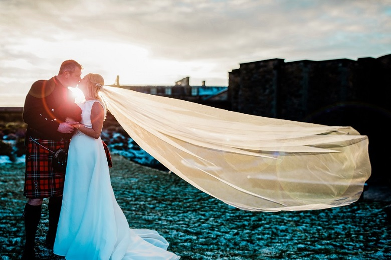 A bride and groom kiss outside Edinburgh Castle with the Bride's veil blowing in the wind