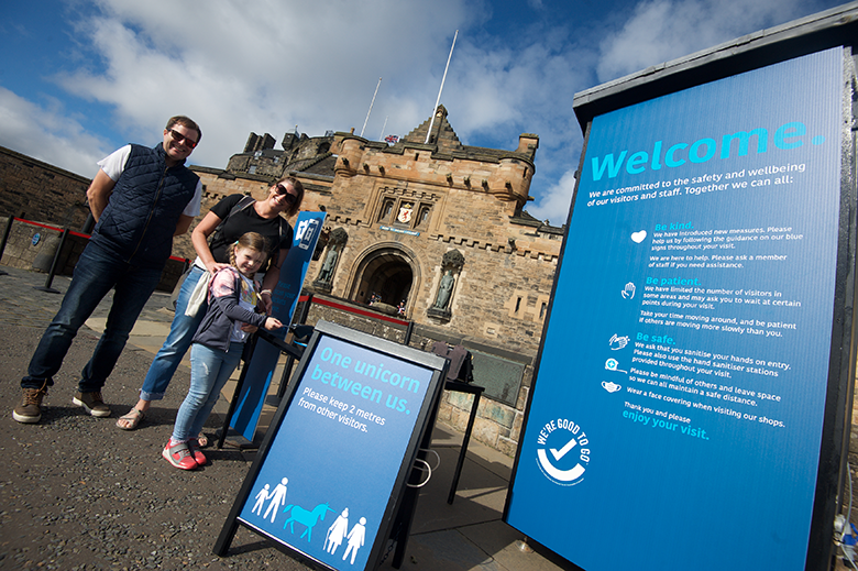 a family arrives at the entrance to Edinburgh Castle, where Covid safety measures and messaging are in place