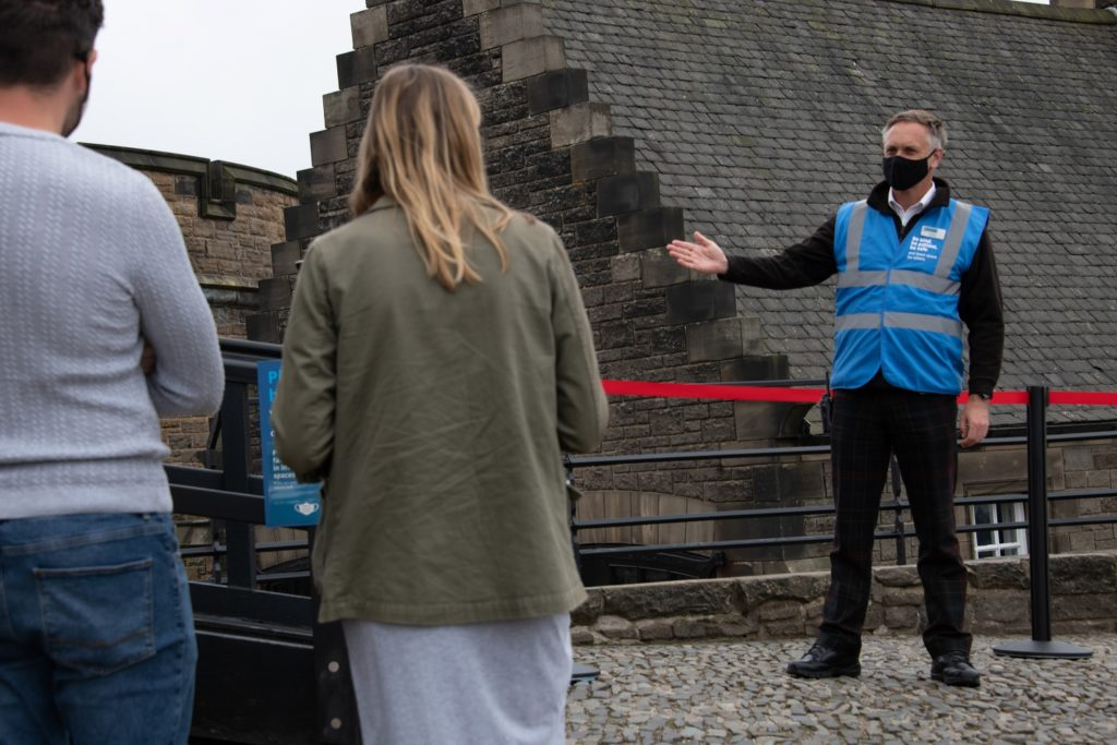 A member of staff in a blue jacket and a black face mask welcomes two visitors to Edinburgh Castle