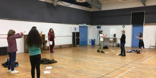 A group of children rehearsing for a play in a school hall
