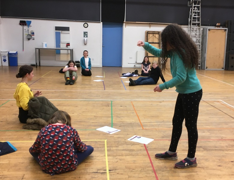 Children rehearse for a play inside a school hall