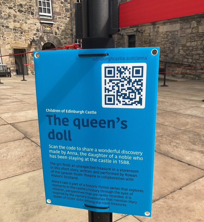 A sign within Edinburgh Castle featuring a QR code for visitors to scan