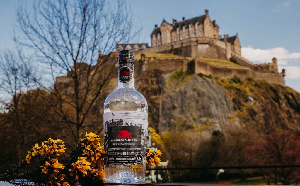 bottle of gin with a castle on a hill behind it