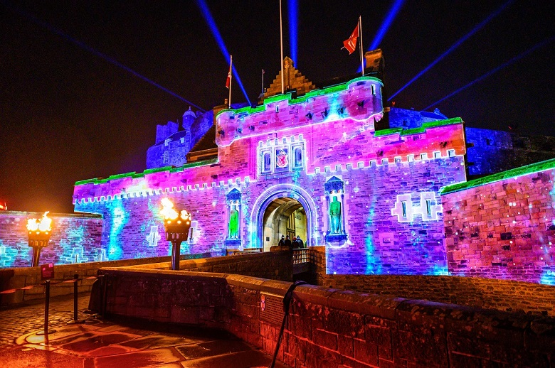 The main entrance to Edinburgh Castle spectacularly illuminated with colourful lasers and projections