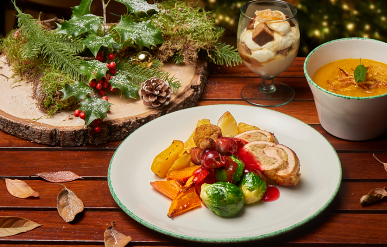 A festive-themed meal on a table adorned with rustic decorations including holly. The food includes soup, roast turkey, brussels sprouts and a decadant chocloate-based dessert served in a tall glass.