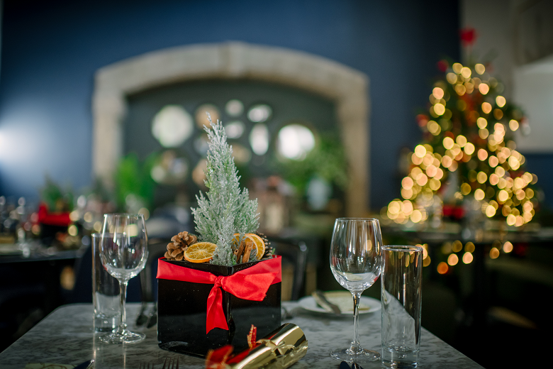 A dining table which has been elegantly decorated for a Christmas meal. A Christmas tree stands to one side of the table.