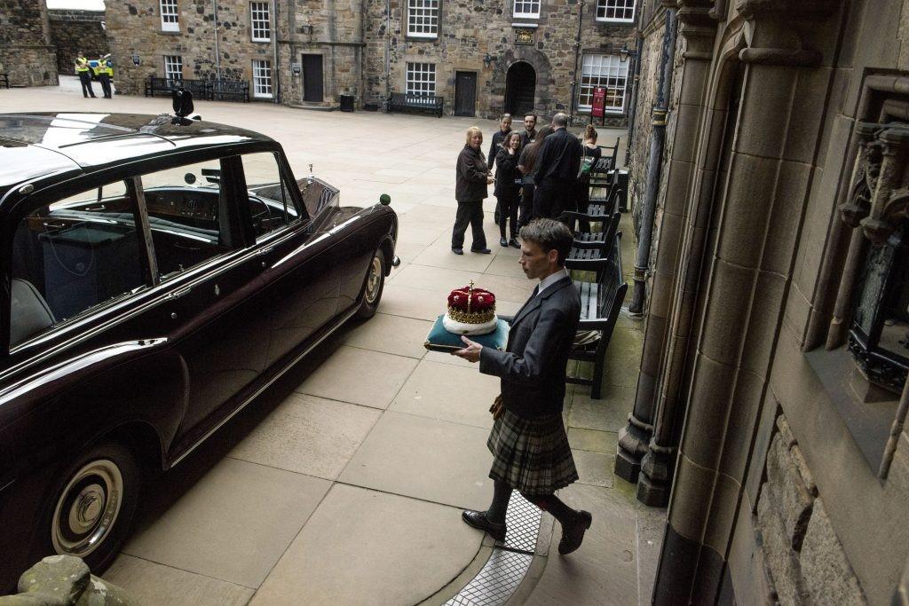 man in kilt carrying crown on cushion towards car