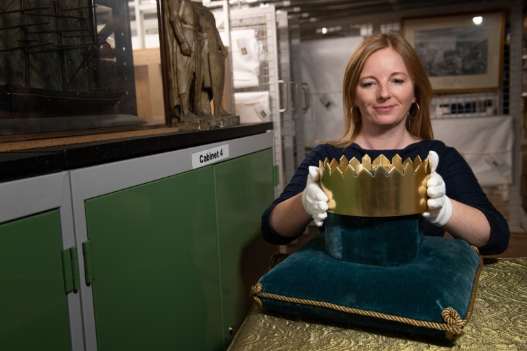 woman wearing gloves placing a crown on a cushion